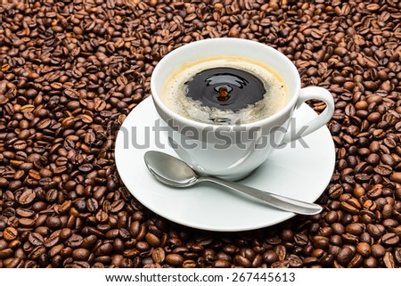 hot coffee cup with a drop of coffee on beans