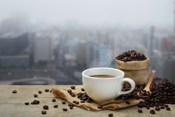Hot coffee cup with coffee bean roating on the wooden table and the city background with copy space