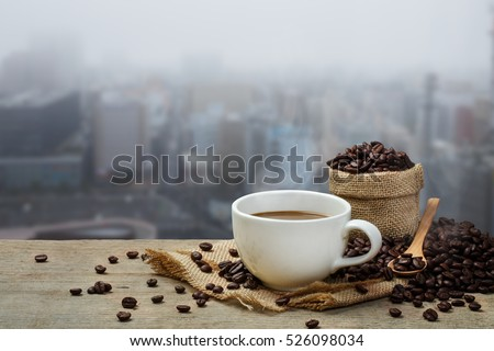 Hot coffee cup with coffee bean roating on the wooden table and the city background with copy space #526098034