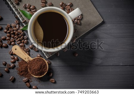 Hot coffee cup with premium arabica coffee beans  on the wooden table.