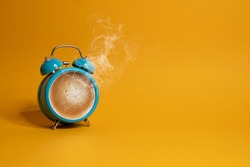 Hot coffee in a blue retro alarm clock on yellow background. Waking up with alarm and coffee concept.