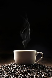 Hot coffee in a white coffee cup and many coffee beans placed around on a wooden table in a warm, light atmosphere, on dark background, with copy space.