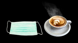 Hot Coffee in porcelain cup and aroma stream  with  surgical mask in cafe  , Medical protective mask on black ,