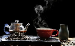 Hot coffee in red coffee cup with steam,  glass coffee pot, milk jug and roast coffee beans on black stone plate with wooden table floor in dark vintage tone style, hot drink concept