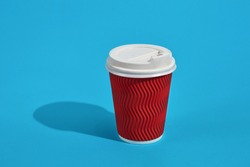 Hot coffee in red paper cup with white lid on blue background wi