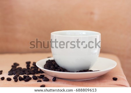 Hot coffee in white cup and coffee beans on the table