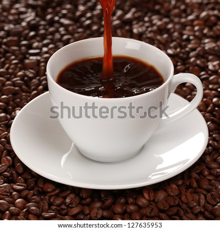 Hot coffee is pouring into a coffee cup