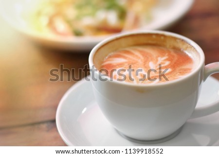 Hot coffee on wooden table, The best materials for processing fresh coffee. porcelain coffee cup on table with breakfast, blurred and free space for text. Industrial food and drink background concept.