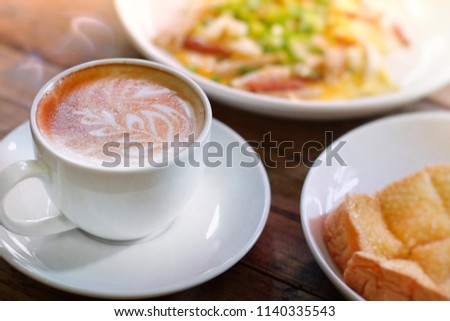 Hot coffee on wooden table, The best materials for processing fresh coffee. porcelain coffee cup on table with breakfast, soft focus, free space for text. Industrial food and drink background concept.