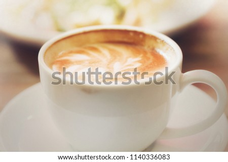 Hot coffee on wooden table, The best materials for processing fresh coffee.Porcelain coffee cup on table with breakfast, soft focus, free space for text. Industrial food and drink background concept.