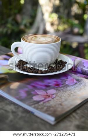 hot coffee, smoke on surface coffee mugs  ,cup of coffee on magazine.