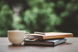 Hot coffee, smoke, with books and pen for note taking with beautiful nature background.