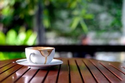 hot coffee that has almost been drunk on wood table with soft-focus and over light in the background