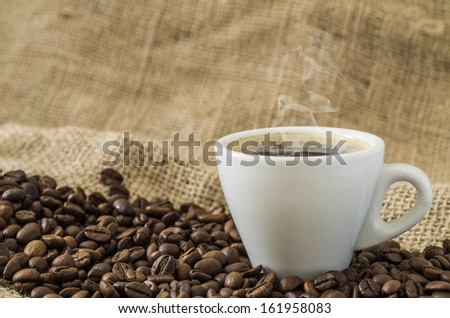 Hot coffee with coffee beans in a great background