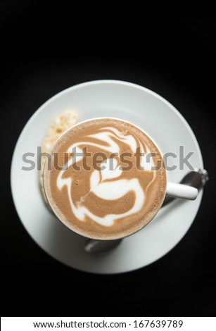 Hot coffee with latte art  with latte art on black table