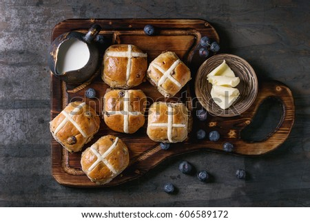 Hot cross buns on wooden cutting board served with butter, knife, fresh blueberries and jug of cream over old texture metal background. Top view, space. Easter baking. #606589172