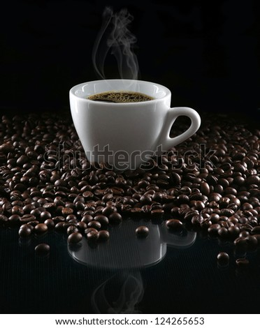 Hot cup of coffee and beans on a dark background