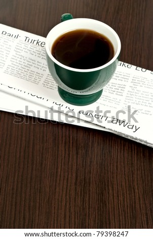 Hot cup of coffee and newspaper on dark desk