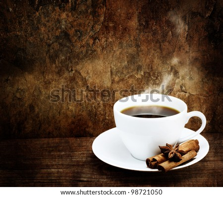 Hot Cup of Coffee in White Mug with Cinnamon and Star Anise in Grunge - Vintage Style - stock photo