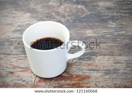 Hot Cup of Coffee on a grungy Wooden Table