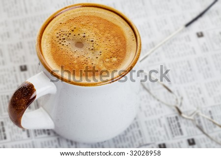 Hot cup of coffee on a newspaper with glasses