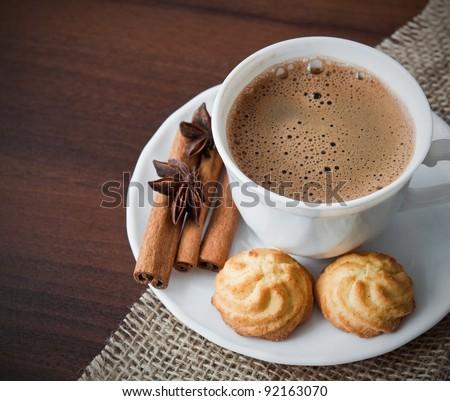 Hot cup of  coffee  on sack with cookies