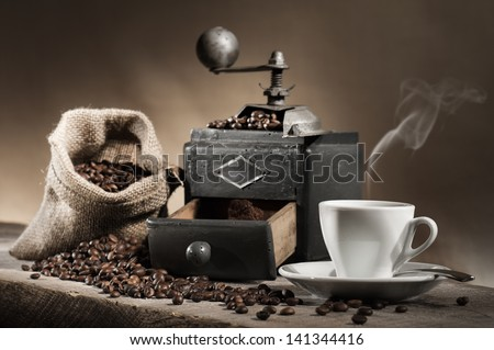 hot cup of coffee with coffee grinder and coffee beans in jute bag on wooden table