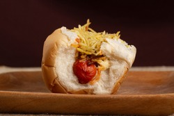 Hot dog in wooden plate showing sausage and shoestring potatoes. Brazilian food.