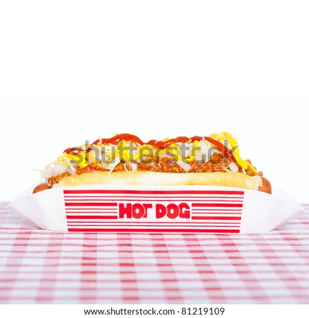 Hot dog with chili, raw onion and sauces on a tablecloth