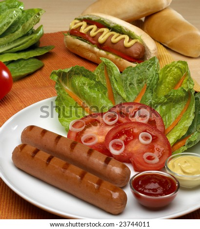 Hot dog with tomatoes, lettuce and sauces