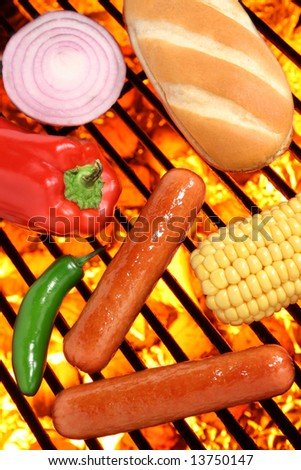 Hot dogs, bun, peppers, onion and corn on a hot barbecue grill