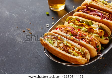 Hot dogs fully loaded with assorted toppings on a tray. Food background with copy space. #1150544471