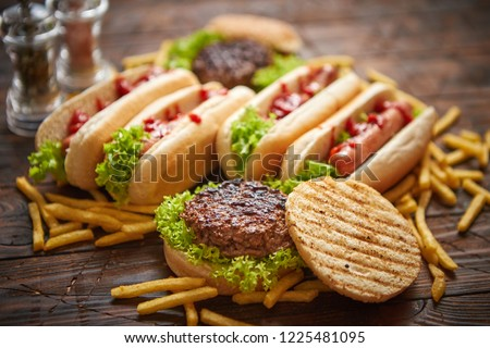 Hot dogs, hamburgers and french fries. Composition of fast food snacks. Placed on rusty wooden table. Top view.