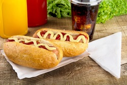 Hot dogs in the tray with ketchup with cola,lettuce on wooden board