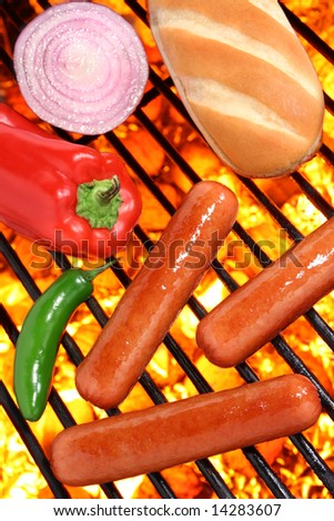 Hot dogs, peppers, onion and bun on a hot barbecue grill