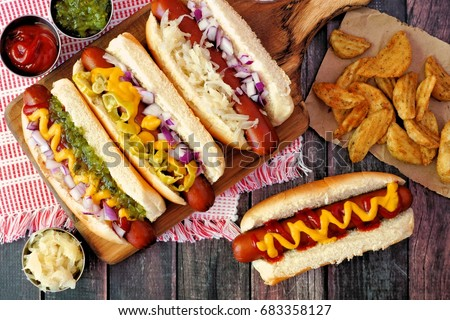 Hot dogs with assorted toppings and potato wedges, above view on a rustic wood background #683358127