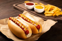 Hot dogs with ketchup, yellow mustard, fries and soda. Image with selective focus