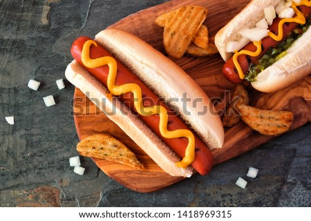 Hot dogs with toppings and potato wedges on wooden board. Close up, top view.