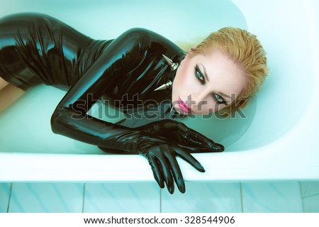 Hot dominant blonde mistress woman in wet shiny latex fetish dress, gloves and spiky leather collar posing in white bath with blue water