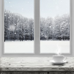 Hot drink in cup on table over winter forest background through window view