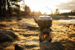 Hot drink in the morning outdoors. Camp kettle and camping stove standing on a rock near the lake. Copy space.