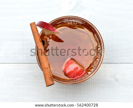 hot drink of apple tea with cinnamon spice stick or mulled wine in glass on wooden background