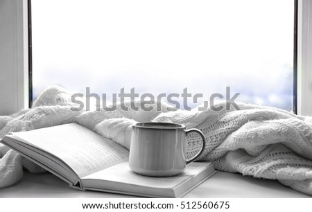 Hot drink with book and plaid on windowsill