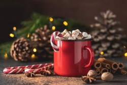 Hot drink with marshmallows and candy cane in red mug. Fir cones, spices in the background. Cozy seasonal holidays