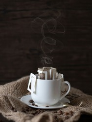 Hot Drip Coffee with Steam. Drip Coffee Still Life, Rustic Country Lifestyle. Espresso with Coffee Beans on Dark Background with Copy Space.