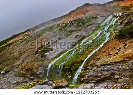 Hot drops of water slowly fall in the stream of the geothermal river on the slope of the volcano. Kuril Islands, Urup Island.