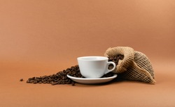 Hot espresso cup and coffee beans in burlap bag on brown background side view. White coffeecup or mug, whole roasted arabica coffea bean in natural jute rustic sack with copyspace