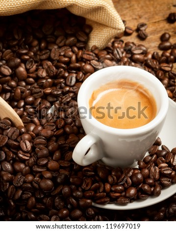 Hot espresso cup with coffee beans on wood table