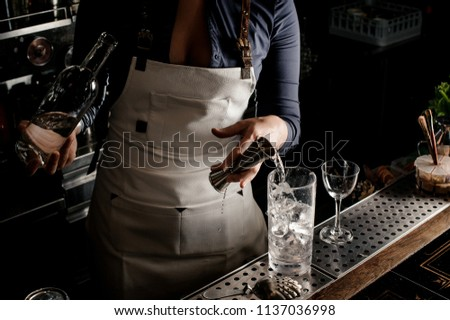 Hot female barman with neckline pouring gin into a cocktail glass for making fresh summer cocktail #1137036998