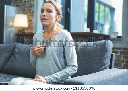 Photo of  Hot flashes. Exhausted mature woman resting on sofa and having hot flash